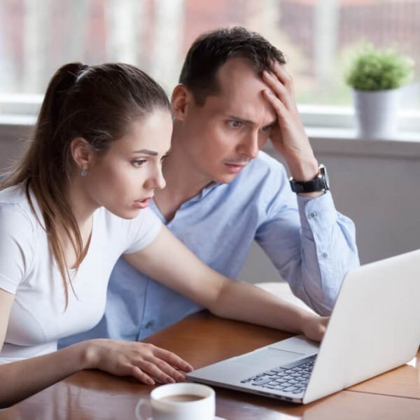 Couple looking at PC after being scammed
